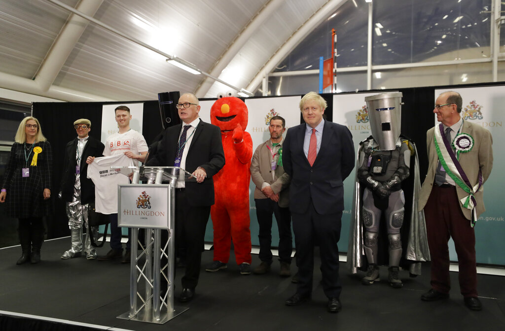 Britain's Prime Minister and Conservative Party leader Boris Johnson stands on stage with other candidates during the Uxbridge and South Ruislip constituency count declaration at Brunel University in Uxbridge, London, Friday, December 13, 2019.