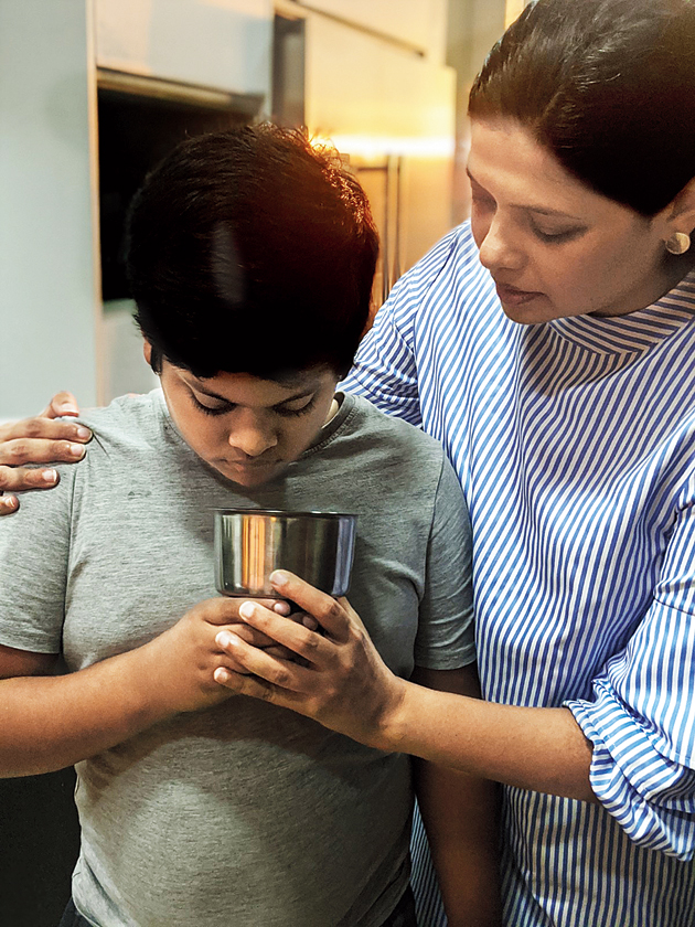 Manjri helps her younger son, Shrehan, to recognise the subtle aroma of spices by smelling them. The 10-year-old helped Manjri ground the spices used in the yellow curry