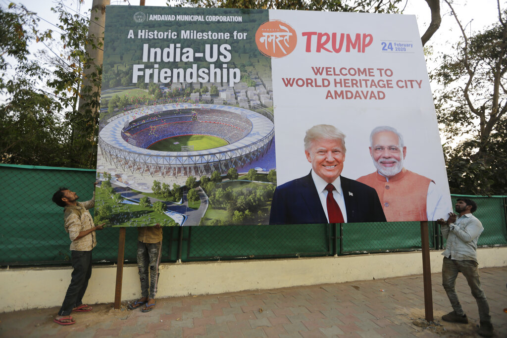 Workers install a hoarding welcoming U.S. President Donald Trump, on the route of his visit to Ahmadabad, on Wednesday