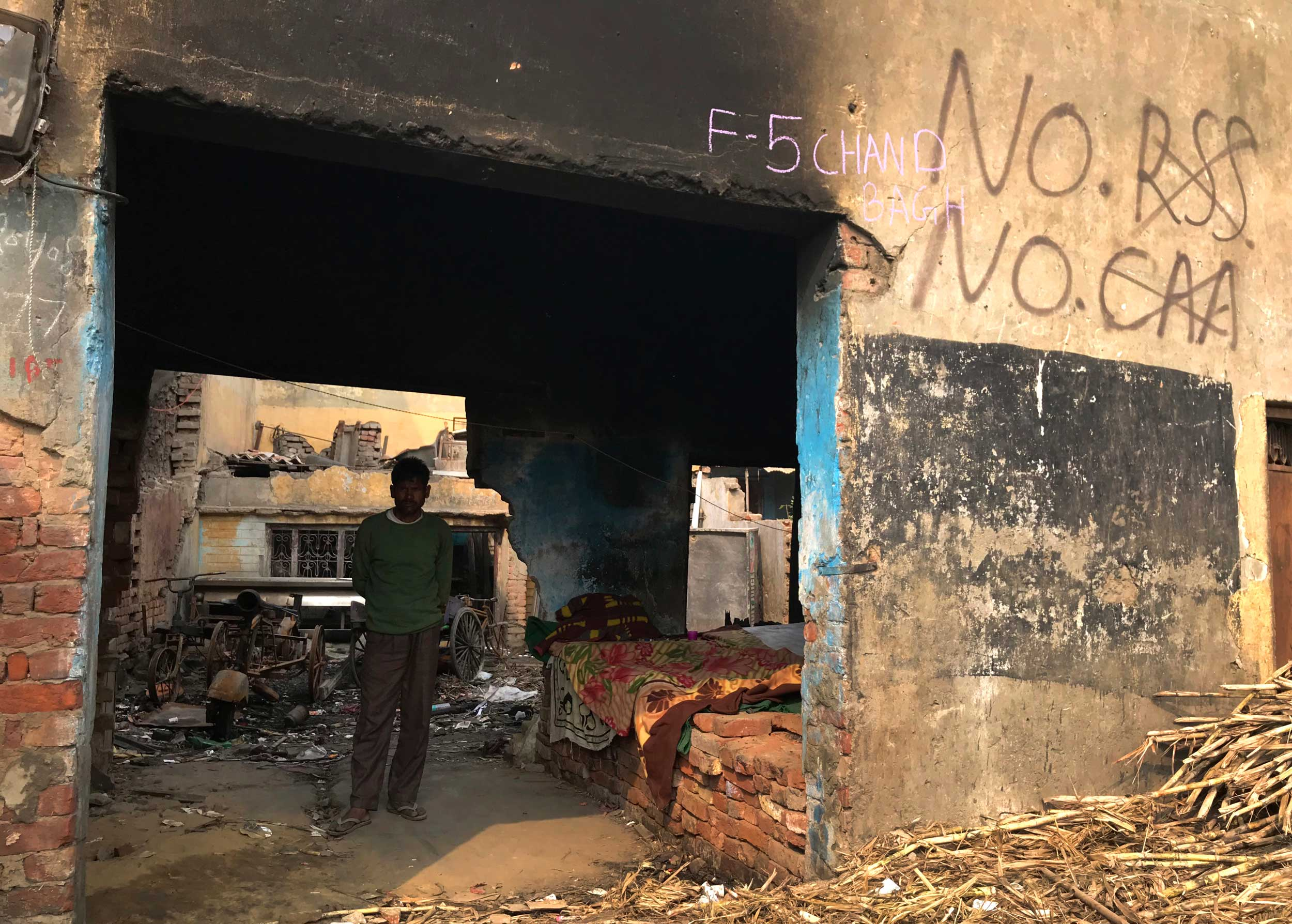 A rickshaw puller stands in front of his rented house burned and ransacked during last week's riots in New Delhi on Monday.