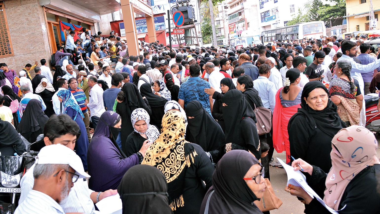 Investors gather outside the office of I Monetary Advisory in Bangalore on Thursday.