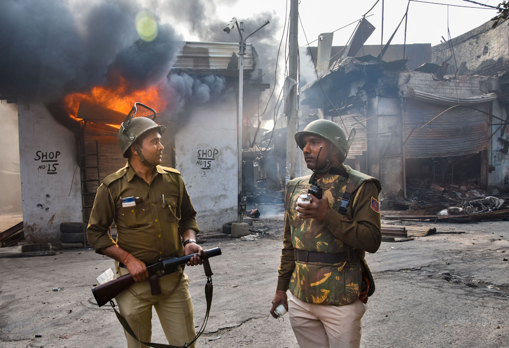Security personnel stand guard near a burning shop in Gokulpuri area of northeast Delhi on Wednesday