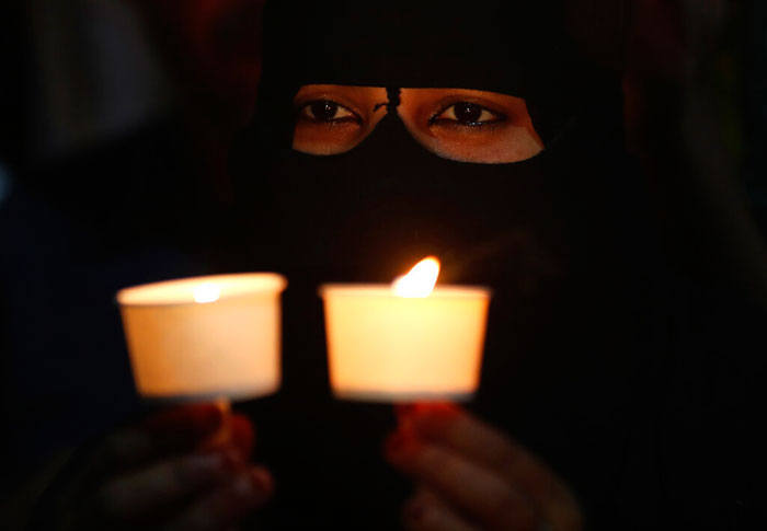 A Muslim woman holds candles during a protest against the sedition case filed by police against a school after a play performed by students denouncing a new citizenship law, in Bangalore, India on Tuesday