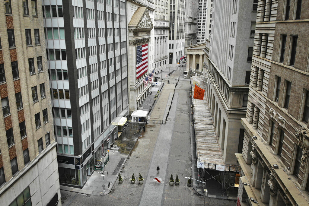 A lone pedestrian wearing a protective mask walks past the New York Stock Exchange as COVID-19 concerns empty a typically bustling downtown area, Saturday, March 21, 2020, in New York. New York Gov. Andrew Cuomo announced sweeping orders Friday that will severely restrict gatherings of any size for the state's more than 19 million residents and will require workers in nonessential businesses to stay home.