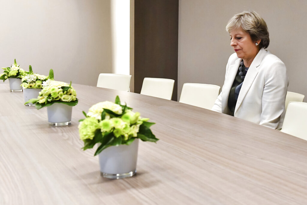 In this Friday, Oct. 20, 2017 file photo Theresa May waits for the arrival of European Council president Donald Tusk prior to a meeting.