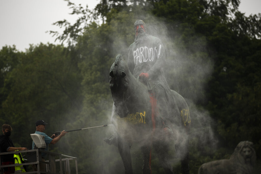 Workers clean graffiti from a statue of Belgium's King Leopold II in Brussels on Thursday, June 11, 2020, that was targeted by protesters during a Black Lives Matter demonstration. The protests sweeping the world after George Floyd's death in the U.S. have added fuel to a movement to confront Europe's role in the slave trade and its colonial past. Leopold is increasingly seen as a stain on the nation where he reigned from 1865 to 1909. Demonstrators want him removed from public view.
