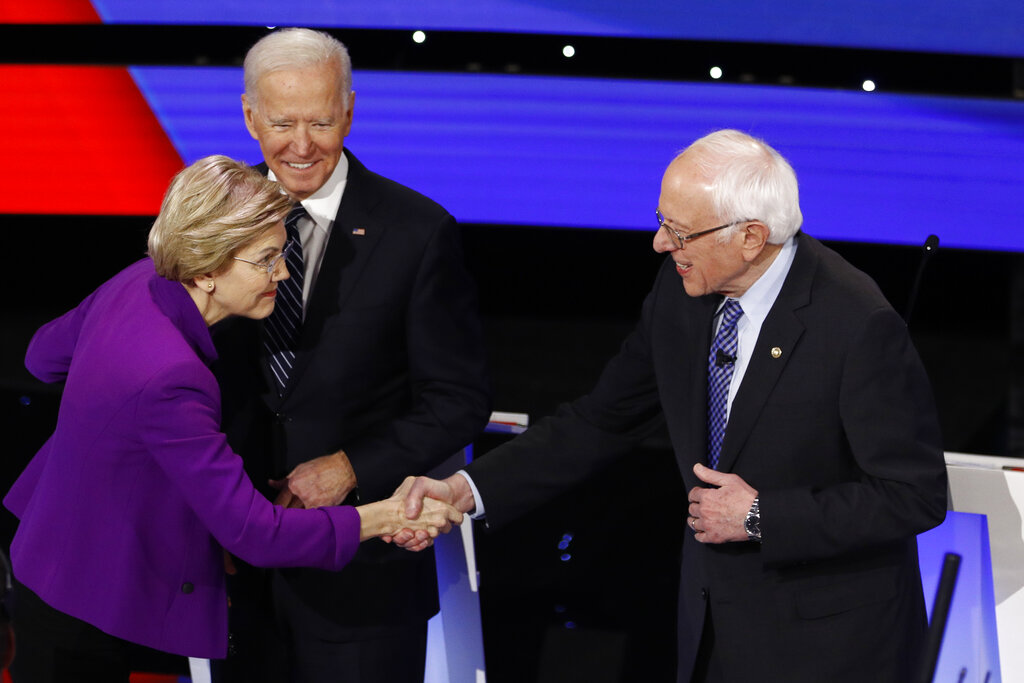 Democratic presidential candidates Sen. Elizabeth Warren, D-Mass., left, and Sen. Bernie Sanders, I-Vt., right greet each other as former Vice President Joe Biden, watches on January 14, 2020, before a Democratic presidential primary debate hosted by CNN and the Des Moines Register