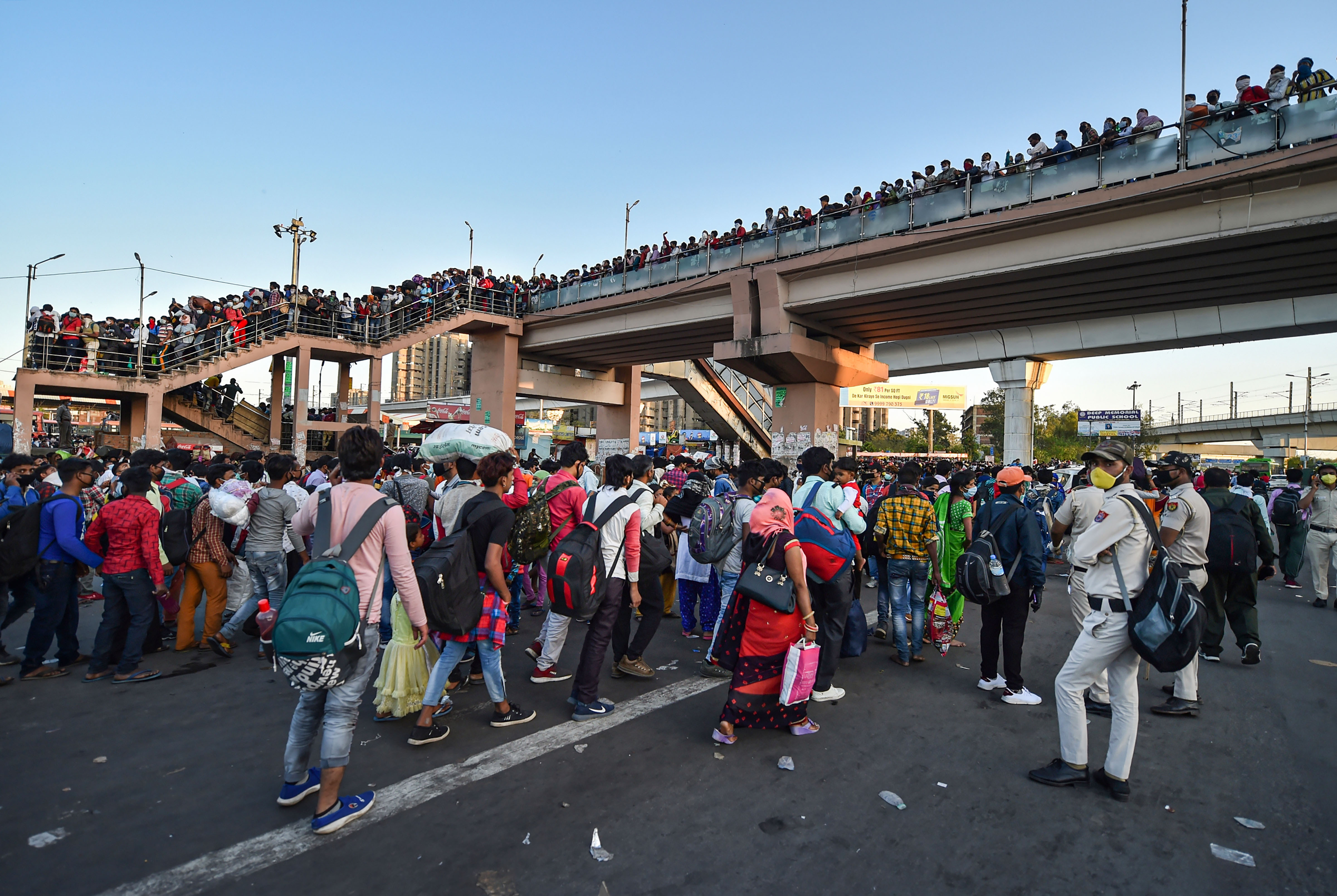Migrants wait to board buses to their native villages during a nationwide lockdown, imposed in the wake of coronavirus pandemic at Kaushambi, in Ghaziabad, Saturday, March 28, 2020