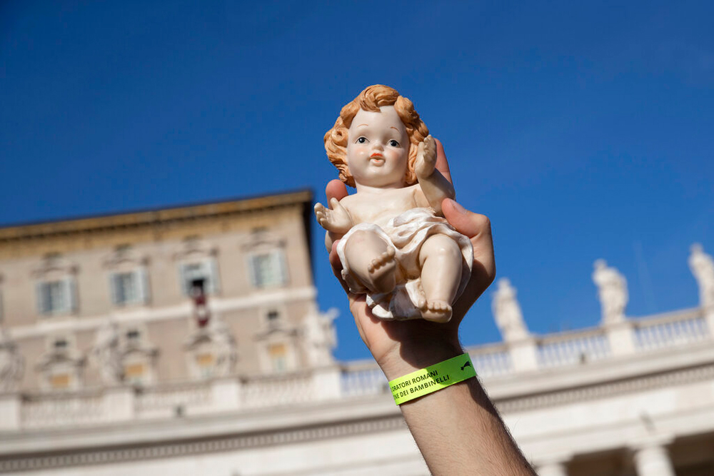 A child holds up a statue of baby Jesus at the Vatican on December 15