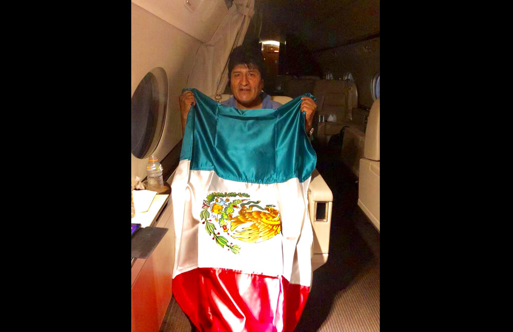 This photo released by Mexico's foreign minister Marcelo Ebrard shows Bolivia's former President Evo Morales holding a Mexican flag aboard a Mexican Air Force aircraft, Monday, November 11, 2019