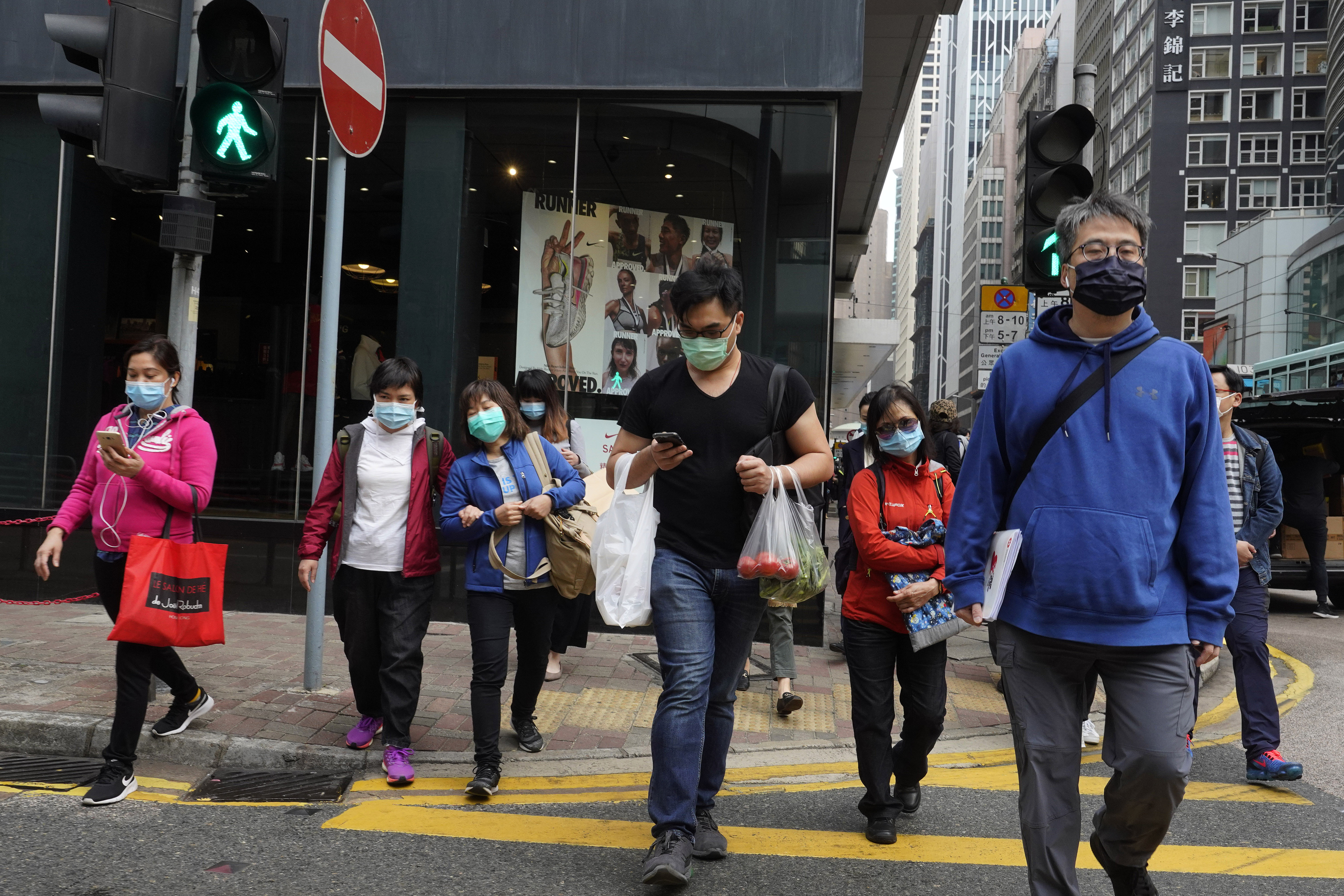 People wearing face masks walk on a street in Hong Kong Tuesday