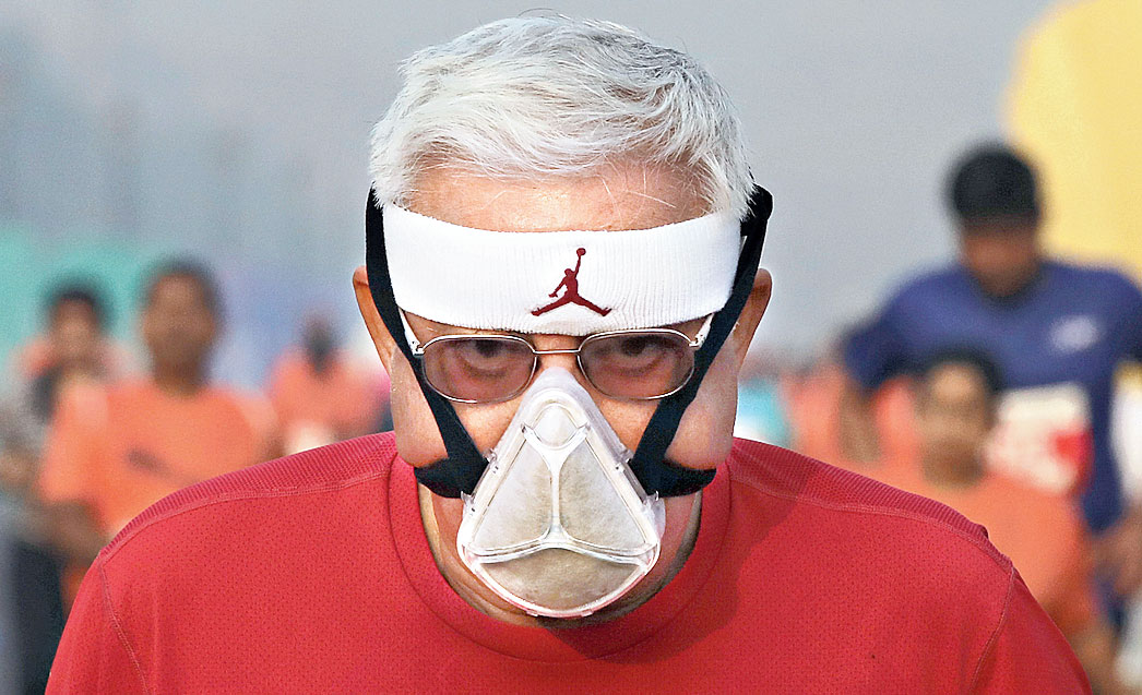 A man wearing a mask takes part in the Delhi half-marathon at Rajpath on Sunday.