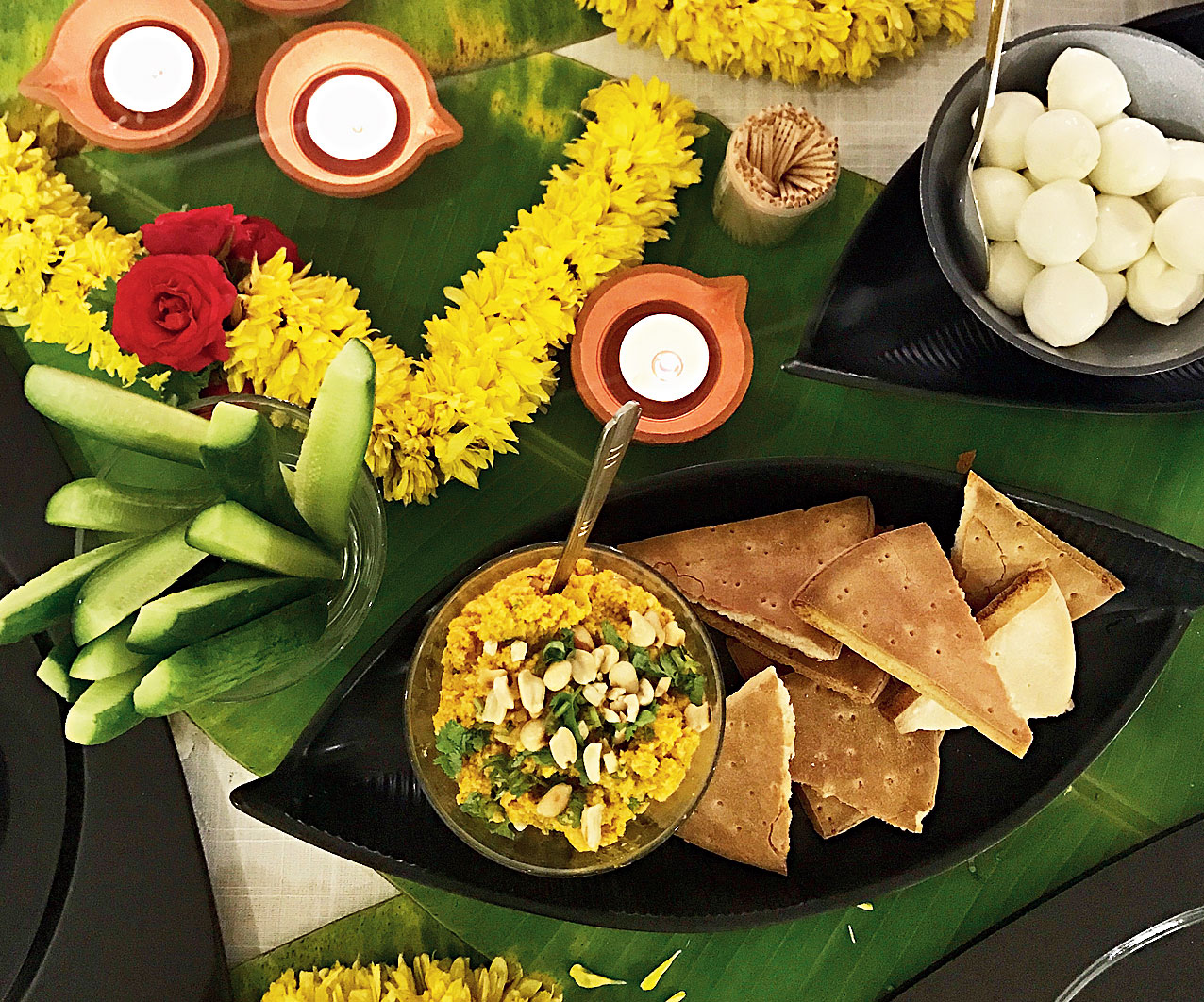 The dining table can be a highlight; decorate it in the traditional way with diyas, flowers and banana leaves