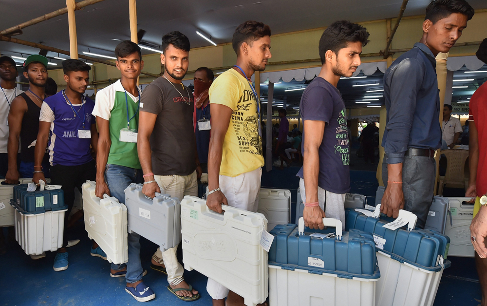 Workers carry EVM and VVPAT machines on the eve of the fifth phase Lak Sabha elections, in Howrah, on May 5, 2019.