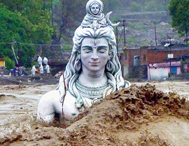 A submerged idol of Lord Shiva stands in the flooded River Ganges in Rishikesh, Uttarakhand, June 18, 2013.
