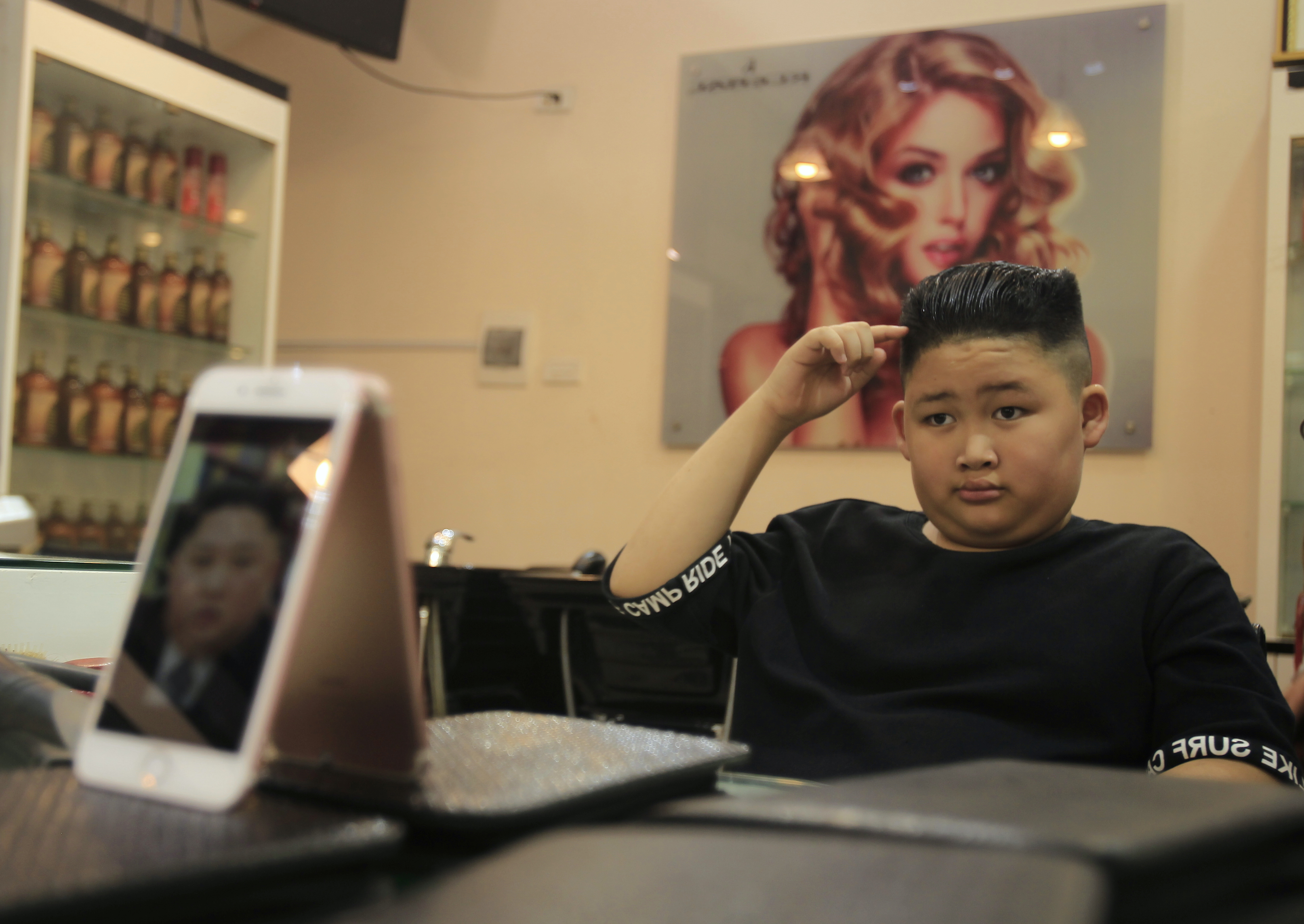 To Gia Huy, 9, checks his hair after getting a Kim Jong-un haircut in Hanoi on Tuesday.