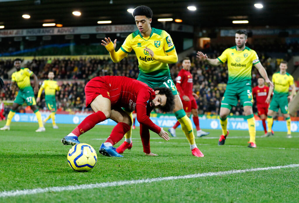 Mohamed Salah, front, duels for the ball with Norwich City's Jamal Lewis during the English Premier League football match between Norwich City and Liverpool at Carrow Road Stadium in Norwich on Saturday