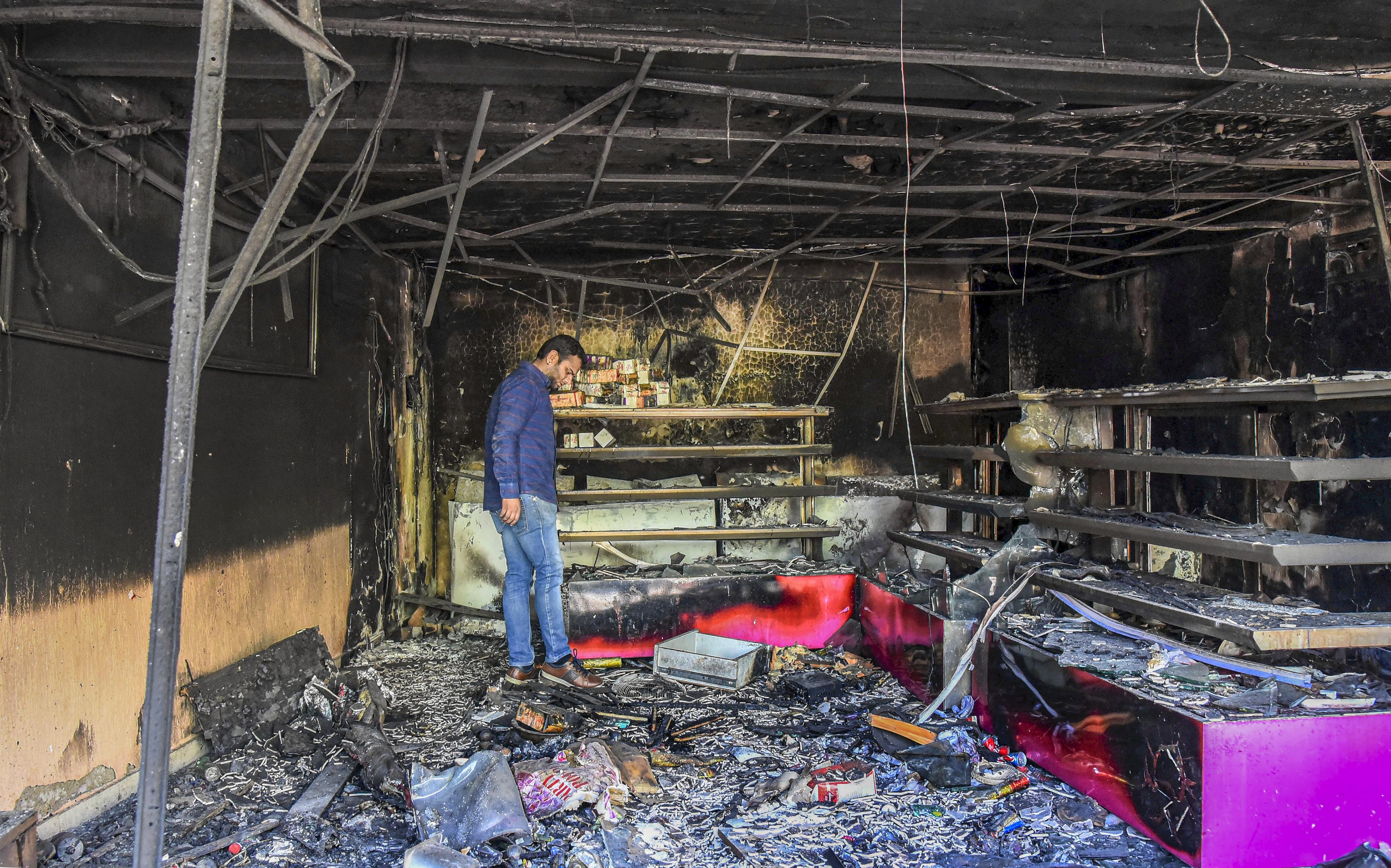 A man stands in a burnt shop which was set ablaze by rioters, in the violence-affected area of northeast Delhi, Sunday, March 1, 2020