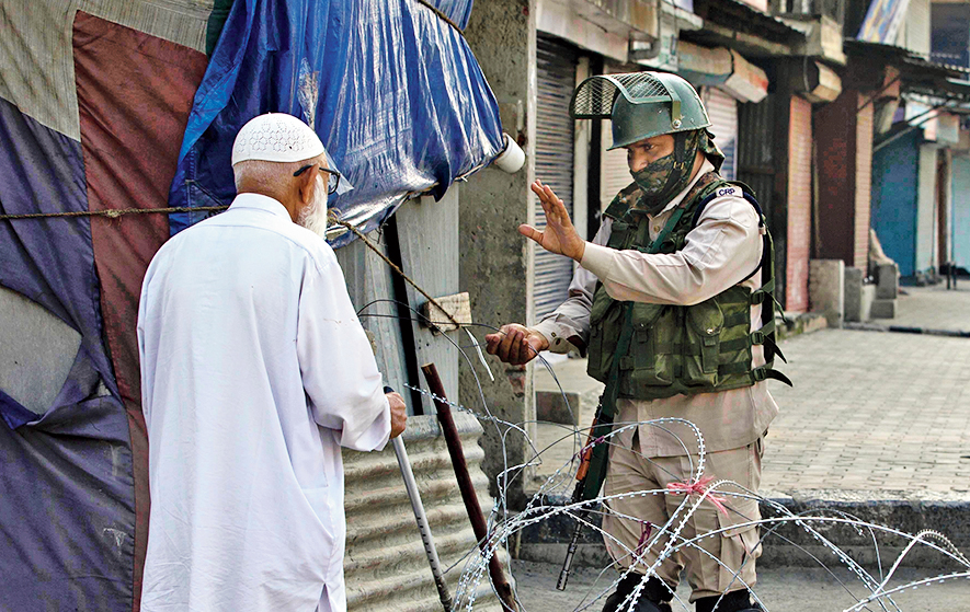An elderly man is stopped before being allowed to pass a checkpoint set up by paramilitary soldiers in Srinagar on Friday.