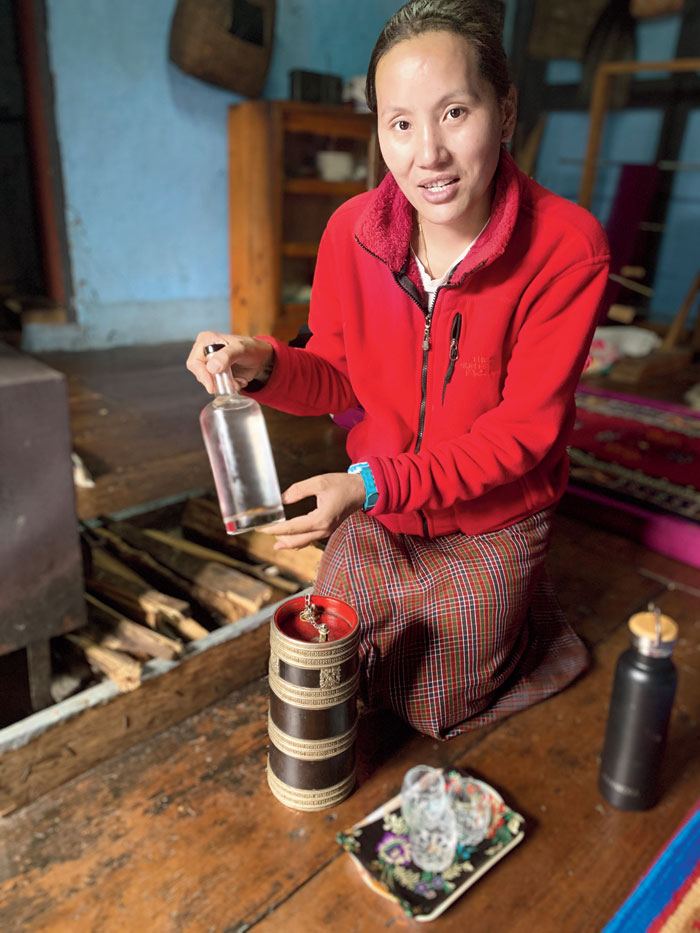 Ngawang Choki serving home-made rice wine at her farmhouse