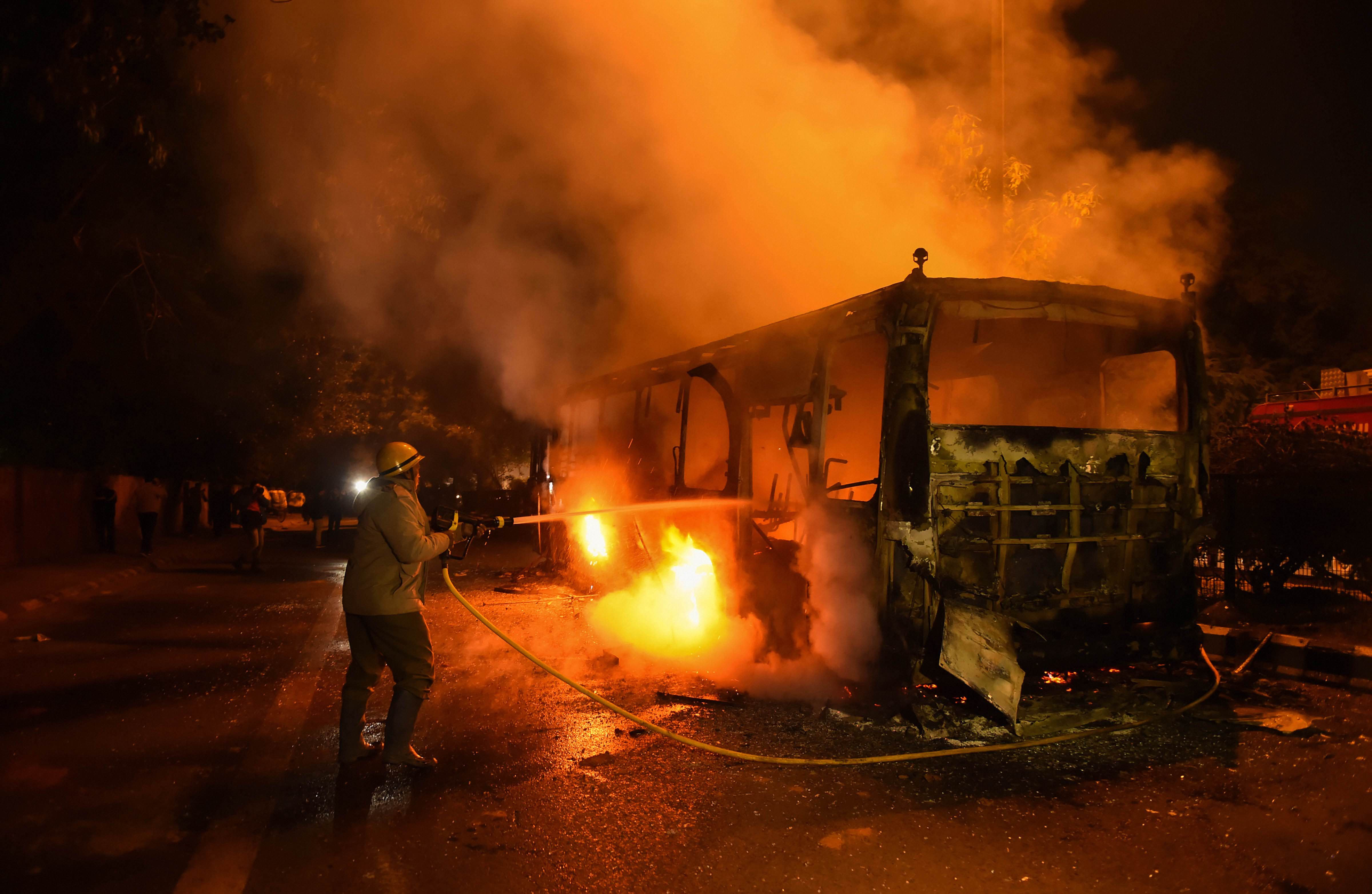 A DTC bus set on fire following protests against the passage of Citizenship Amendment Act near Mathura Road, in New Delhi, Sunday, December 15, 2019.