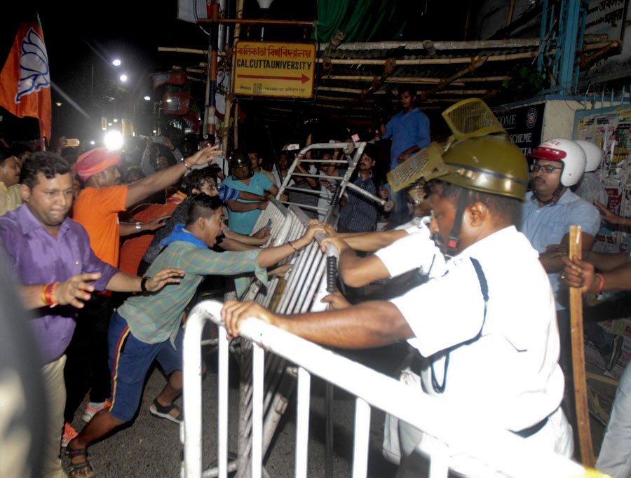 BJP supporters try to storm into the Calcutta University campus on College Street. Lathi-wielding cadres smash guardrails and scuffle with police.