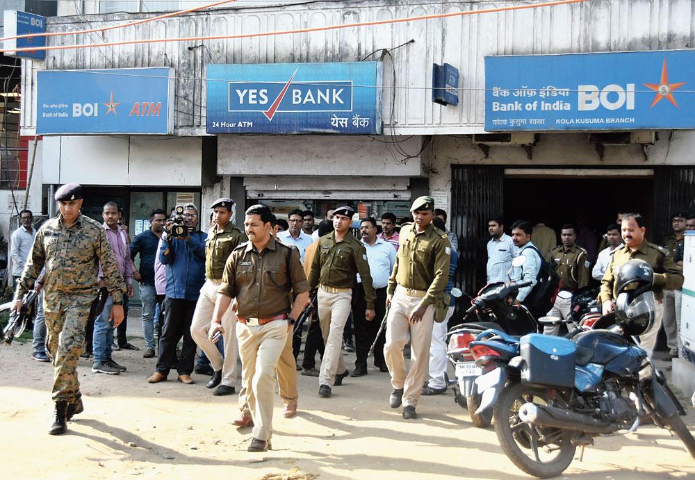 Daylight crime: Police gather outside the bank in Kolakusma, Dhanbad, on Wednesday
