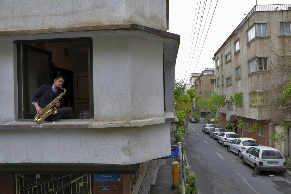 Mohammad Maleklee, 23, of the National Orchestra of Iran and Tehran Symphony, plays saxophone in his window, during mandatory self-isolation due to the new coronavirus disease outbreak, in Tehran, Iran.