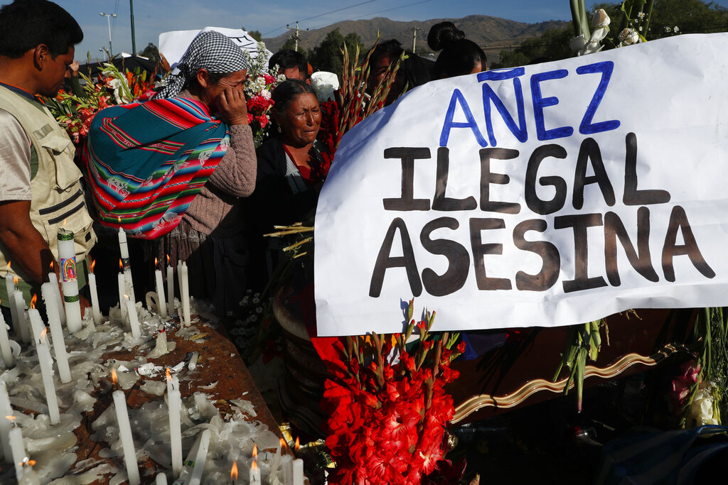 People attend the funeral of supporters of former President Evo Morales killed during clashes next to a banner reading in Spanish