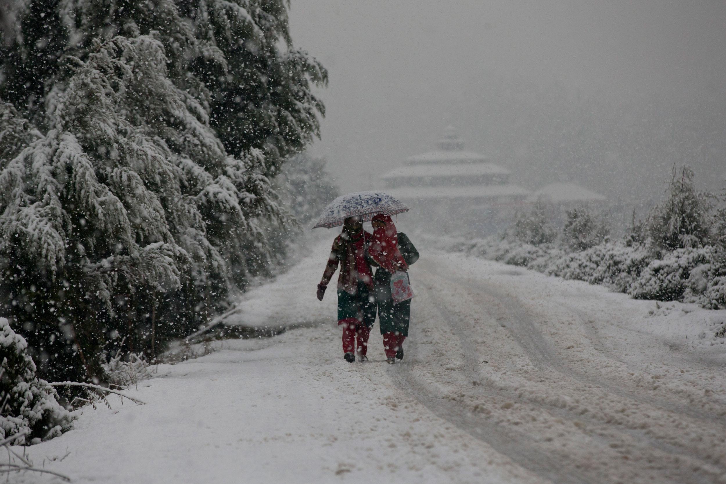 Kashmiri girls walk on a road covered with snow in Srinagar November 7.