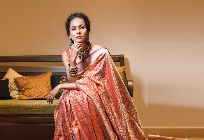 "Elegant is this scarlet Benarasi with intricate design detailing on kadhwa weave. The gold and silver zari brings alive the traditional shikargarh motifs. The look is accessorised with traditional kundan and emerald earrings and neckpiece. ""The rich red Benarasi is the quintessential regal weave. Though the sari has heavy work, it has a weave that settles softly against the skin,"" said Shreevatsa."
