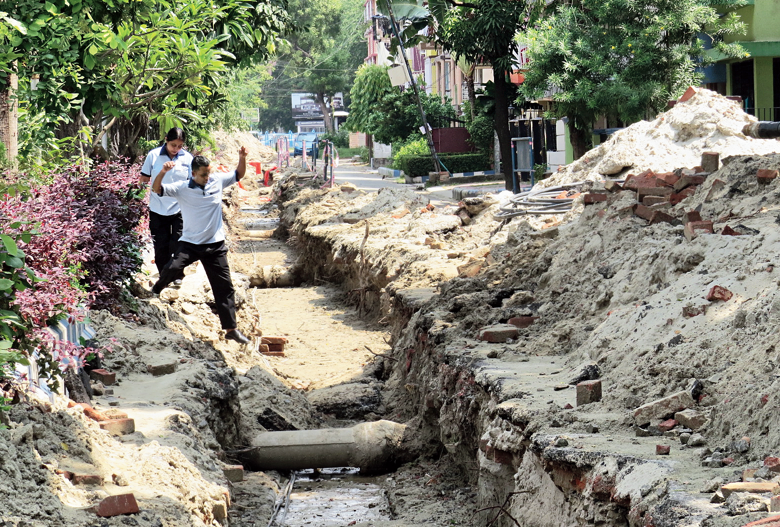 July 4: A worker of a private hospital jumps into a ditch dug up in the service road running parallel to the Broadway in HA Block.