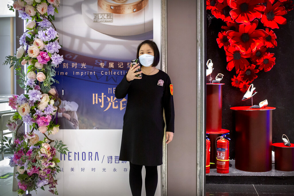 A clerk wears a face mask as she stands outside a store at a mostly empty shopping mall in Beijing, Saturday, March 7, 2020