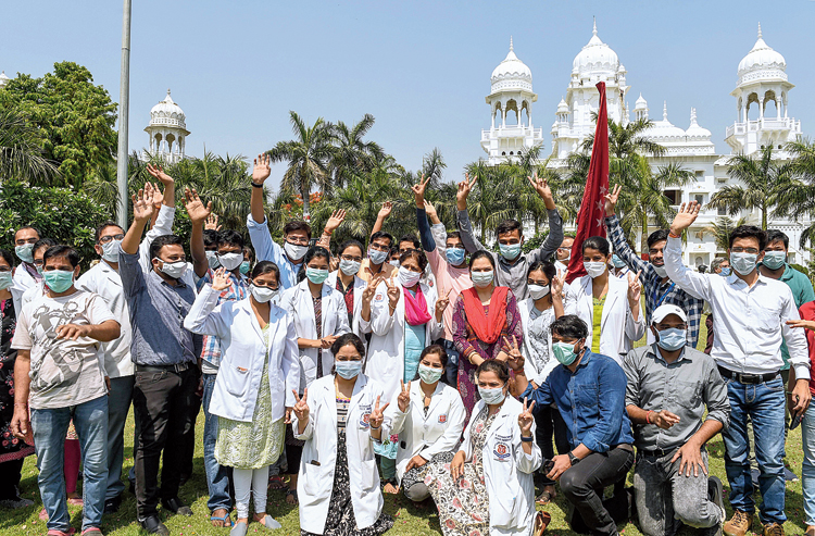 Health care staff at King George's Medical University, Lucknow, acknowledge the flower petals showered on them by the armed forces on Sunday.