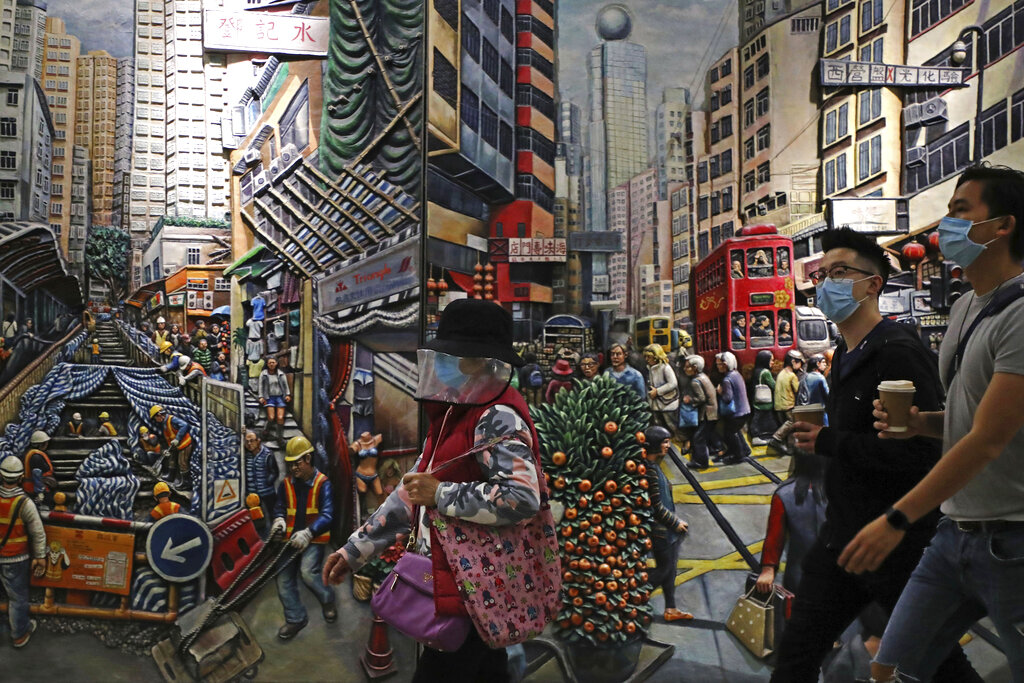 People wearing face masks to protect themselves from possibly contracting the coronavirus COVID-19 as they walk past a painting in Hong Kong, Saturday, April 25, 2020.