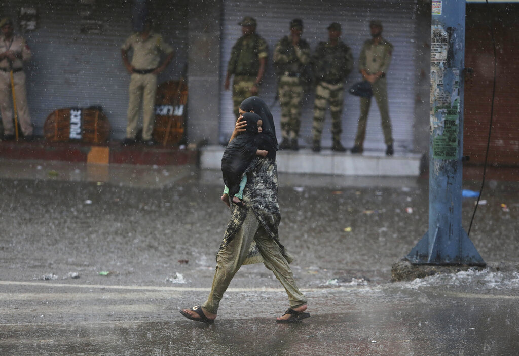 A woman carries her child as she walks past Indian security personnel as it rains during curfew like restrictions in Jammu, India, on Monday, Aug. 5, 2019.