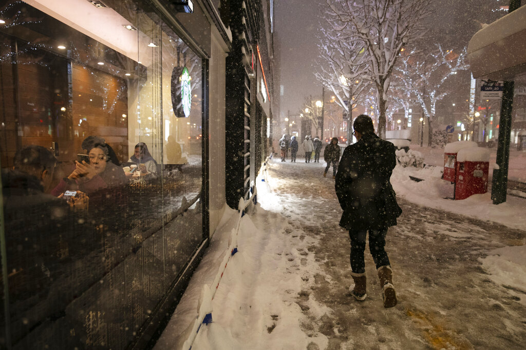 A man walks through a snow storm past a coffee shop Feb. 5, 2020, in Sapporo, Hokkaido, Japan.