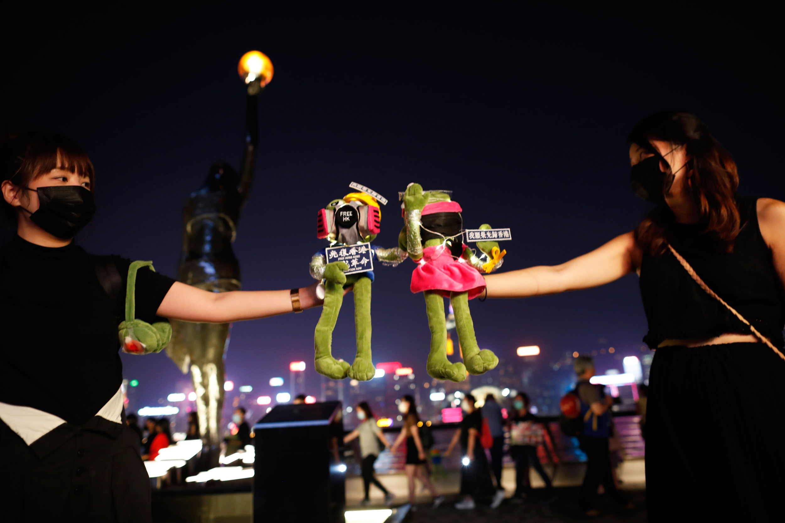 Students hold up 'Pepe the frog' while forming a long human chain at the Hong Kong harbour front on September 30, 2019.