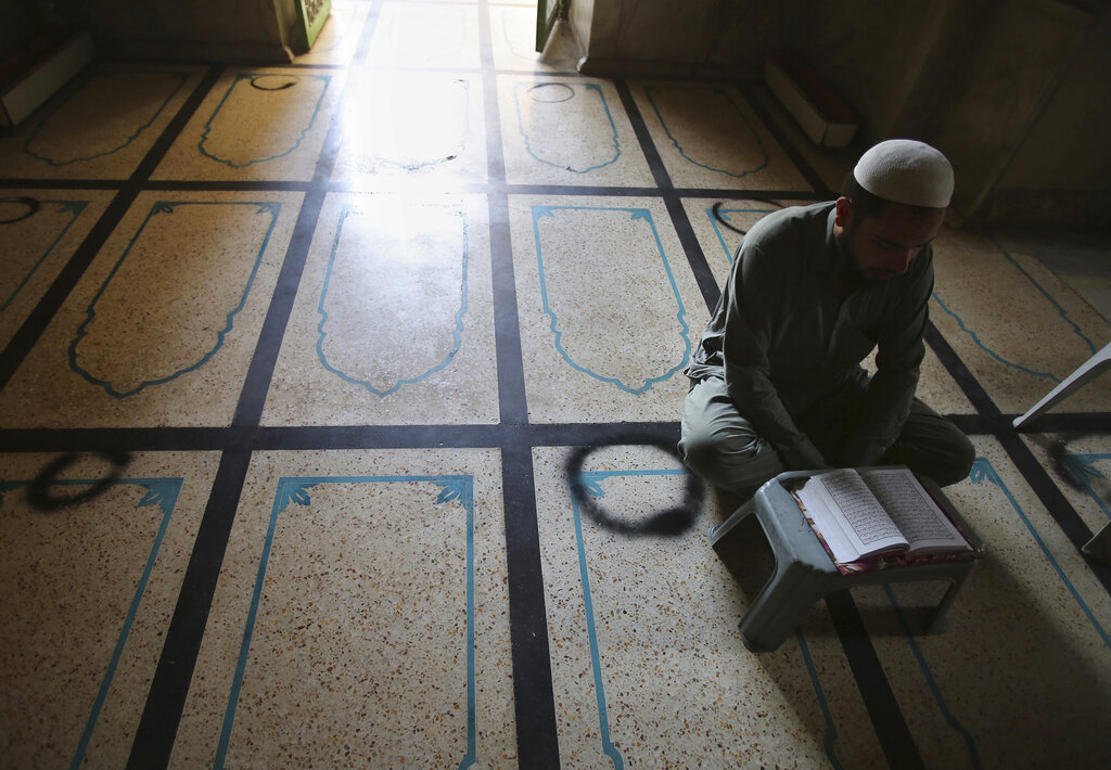 A Muslim worshiper recites the Quran at a mosque during the first day of Ramadan, in Peshawar, Pakistan. Saturday, April 25, 2020.