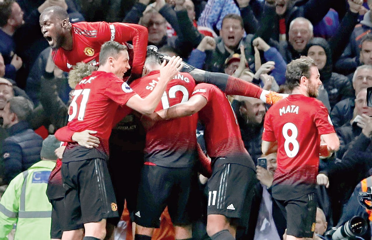 Manchester United players celebrate their third goal on Saturday.