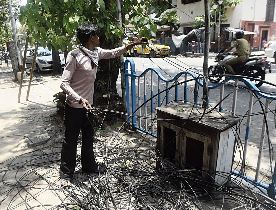 A man removes defunct cables along Harish Mukherjee Road on Thursday.
