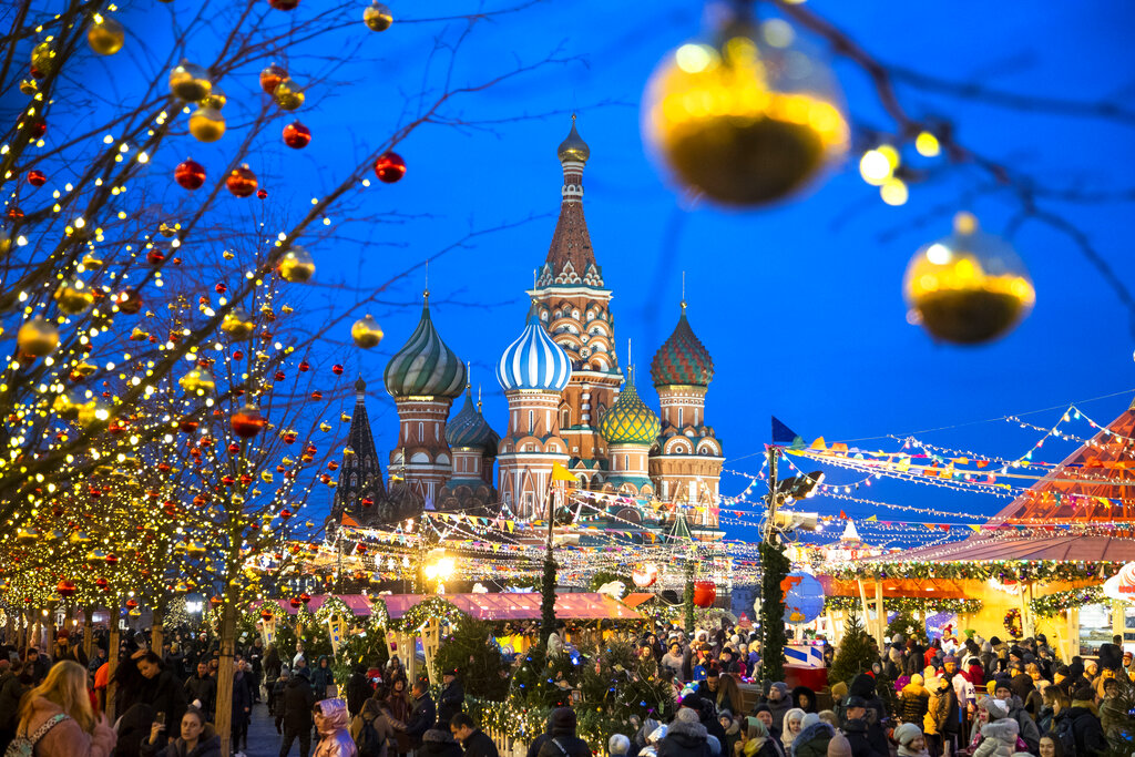 People walk in Red Square decorated for Christmas and New Year celebrations, with the St. Basil's Cathedral in the background in Moscow, Russia.