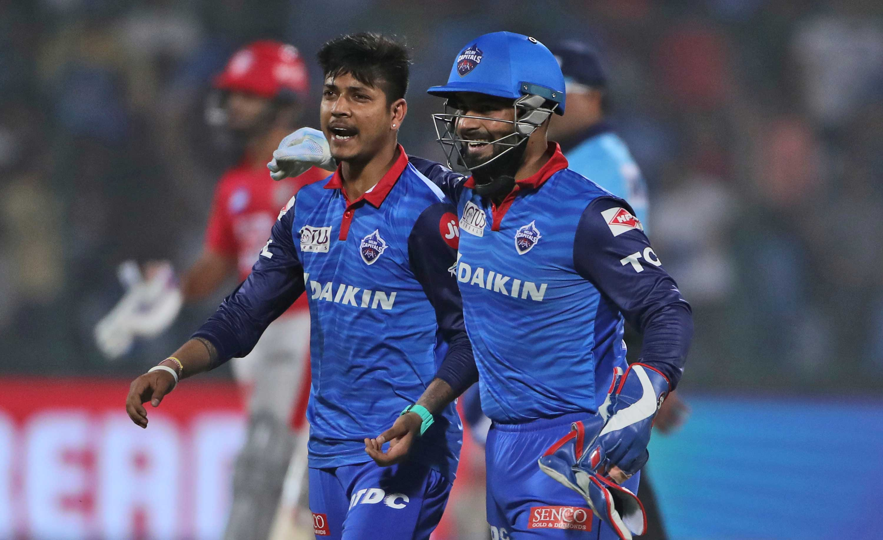 Sandeep Lamichhane (left) and Rishabh Pant celebrate the dismissal of Kings XI Punjab batsman Chris Gayle during the cricket match in New Delhi, on April 20, 2019.
