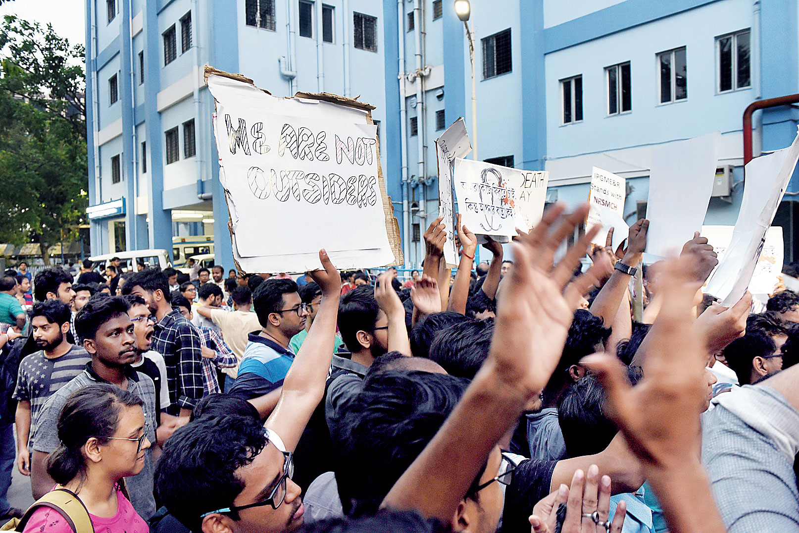 """Protesting doctors hold up a poster that says """"we are not outsiders"""" at SSKM Hospital."""