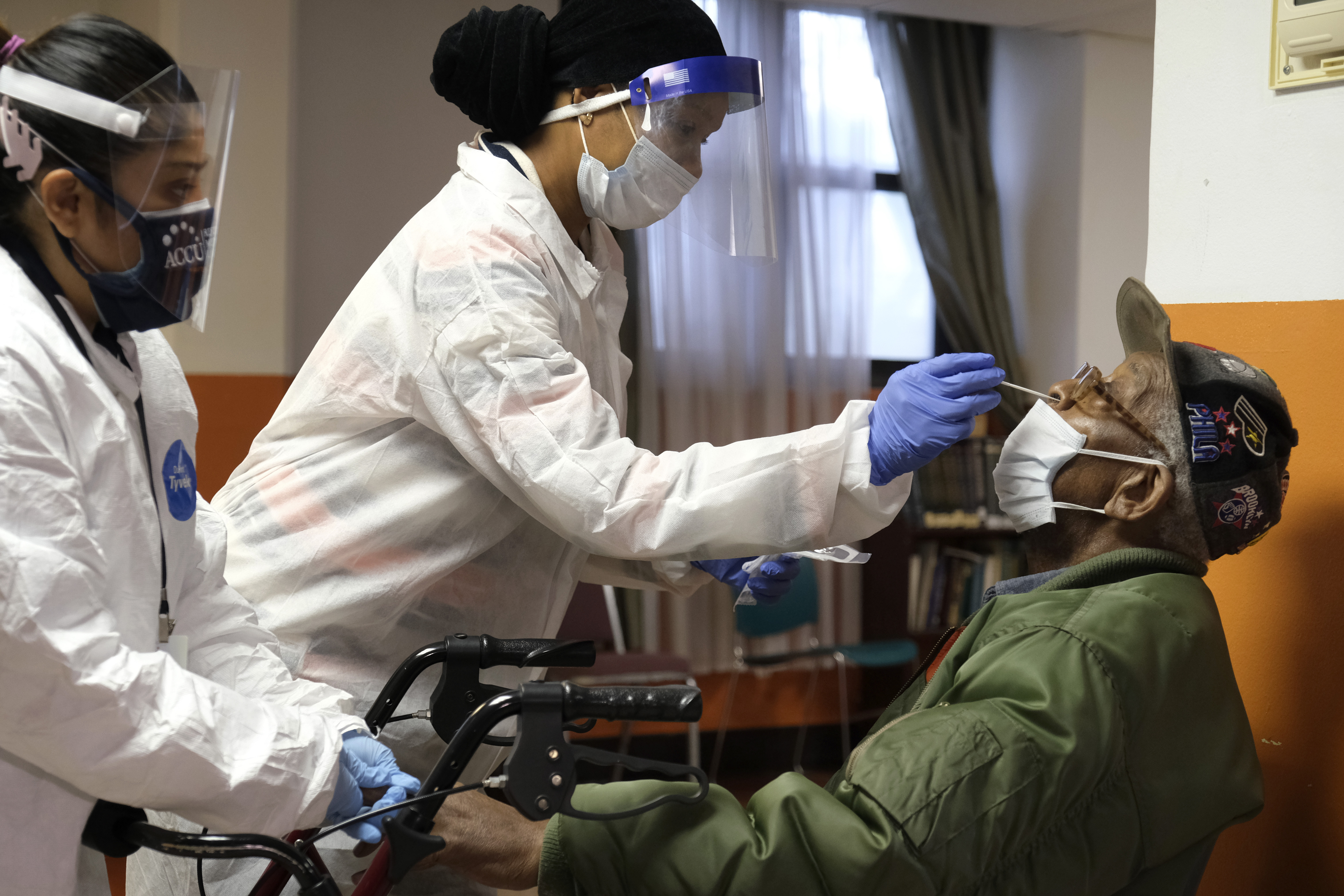Willie Johnson, right, a resident of senior housing, gets tested for Covid-19
