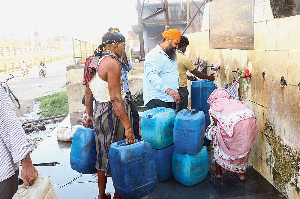 People fetch water from Jusco taps near Mango bridge in Jamshedpur on Wednesday.