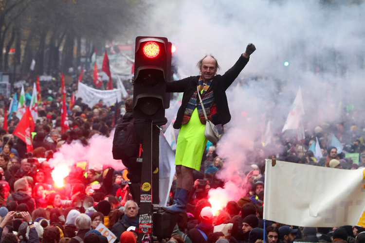 A protester stands on a traffic light during a demonstration in Paris on December 5