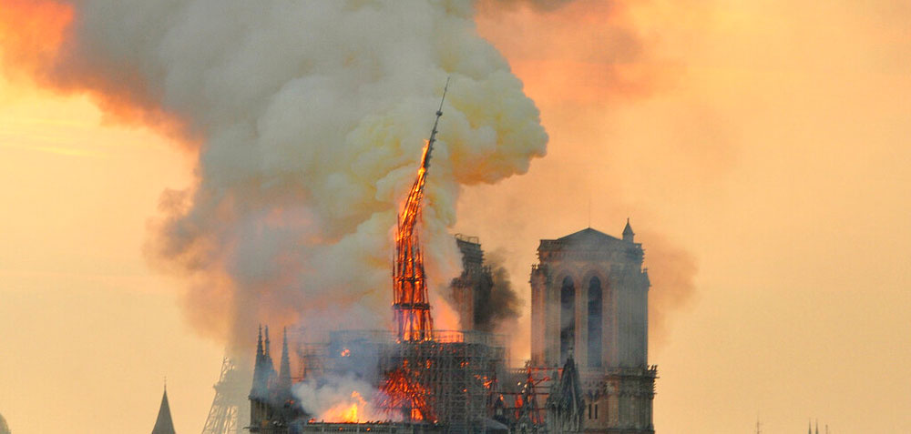 Flames and smoke rise from the blaze as the spire starts to topple on Notre Dame cathedral in Paris on Monday