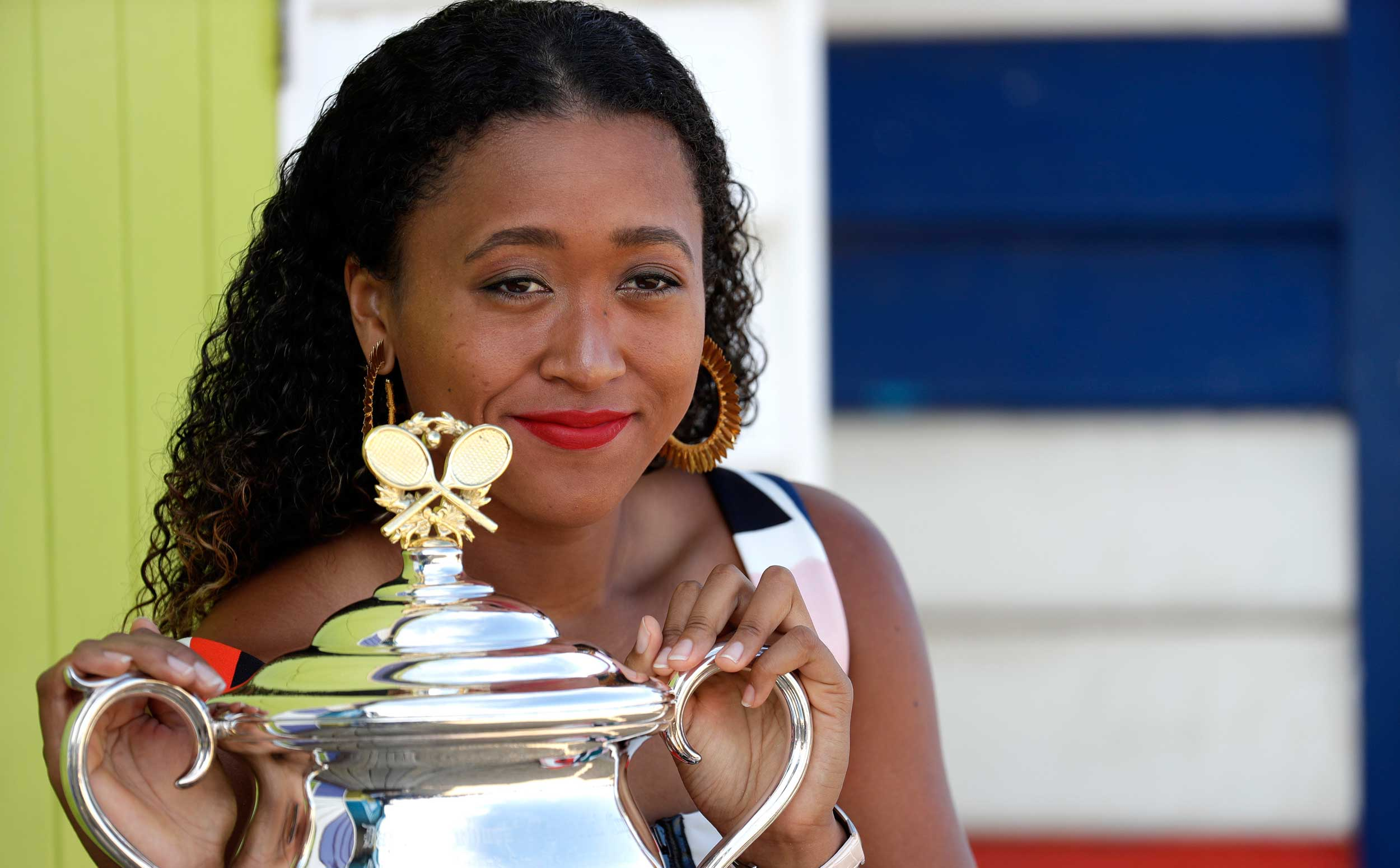 Naomi Osaka poses with her trophy the Daphne Akhurst Memorial Cup at Melbourne's Brighton Beach after her win over Petra Kvitova in the women's singles final at the Australian Open tennis championships in Melbourne, Australia, on January 27.
