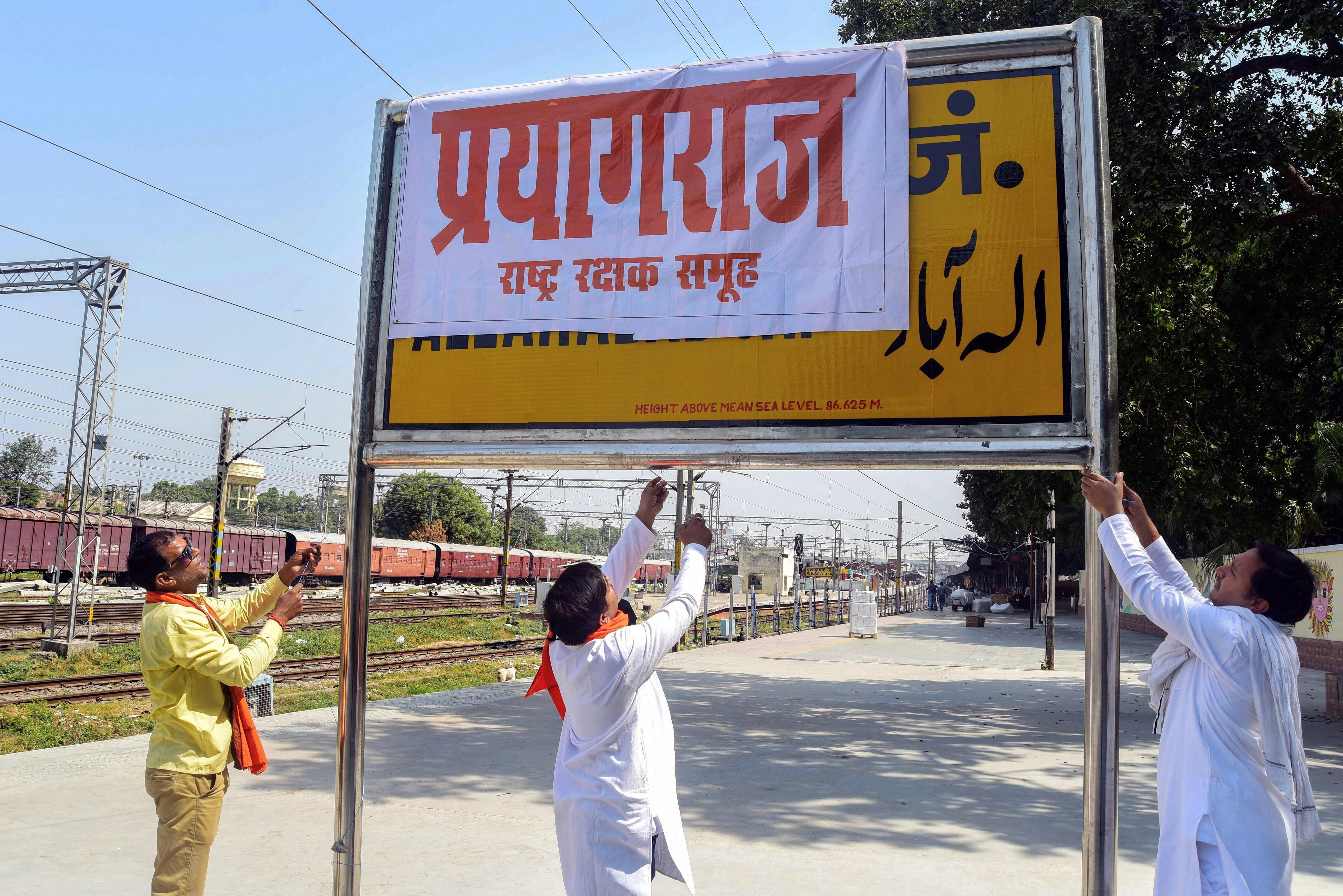 Activists of the Rashtriya Rakshak Samuh cover a railway station sign that says